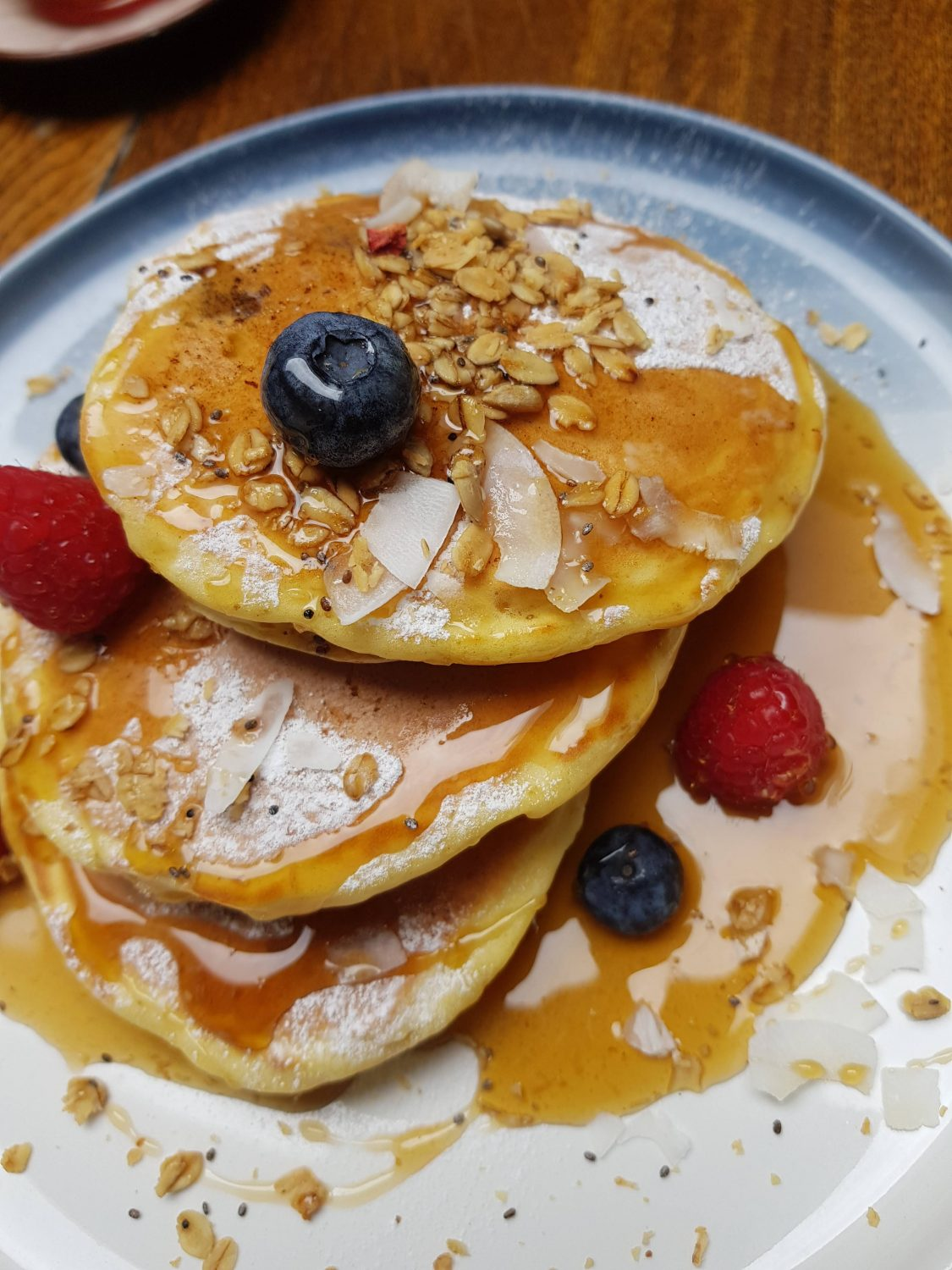 Buttermilk Pancakes with berries, coconut and maple syrup